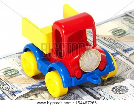 Truck toy on the road from money isolated on white background