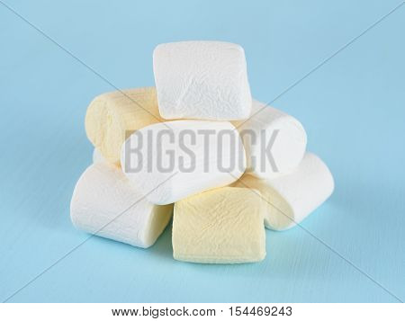 Pile of marshmallow on blue table close-up