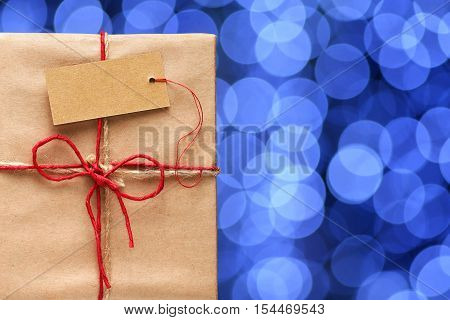 Gift box with tag on background of blurred blue lights