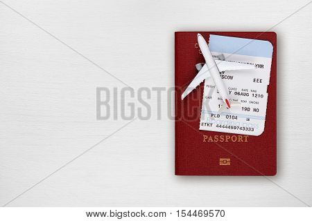 Passport boarding pass and toy airplane on table top view