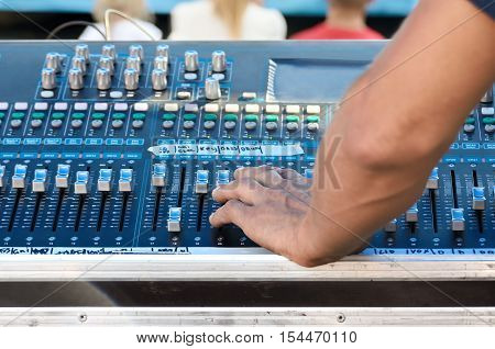 Sound technician adjusts the sound in professional equipment.