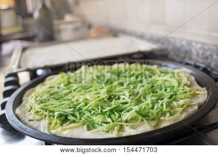 preparation of home made pizza with stick zucchini