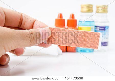 Hand holding plaster with betadine alcohol gauze dressing and bandages on white background