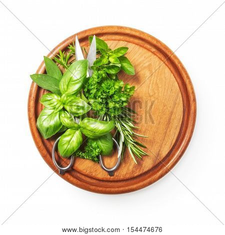 Kitchen herbs on cutting board. Fresh basil parsley peppermint rosemary and scissor. Single object isolated on white background clipping path included. Top view flat lay