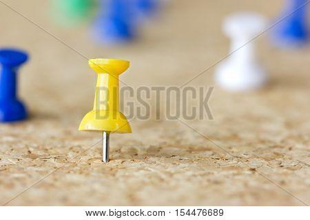 Closeup image of a yellow pushpin on a cork board.