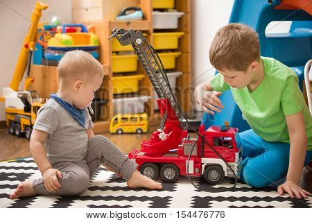 Siblings boys playing with a toy fire truck in kids room. Children playing cars in their room. Leisure activities at home. Playground. indoors. Profession. Fireman.