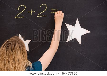 Young girl drawing question mark on a black background. woman drawing question mark for the math task on the board. Teacher hand drawing question mark on chalkboard. Education back to school concept