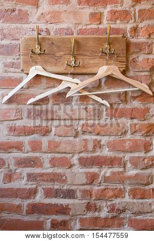 Wooden hangers on the old bricks wall background. Clothes hangers in cafe.