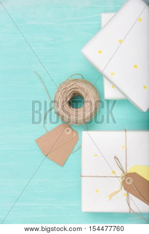 Top view on a nice present packed in white paper with small yellow stars on turquoise background. Wrapped gift for birthday party. Flat lay. Mock-up. Holidays concept.