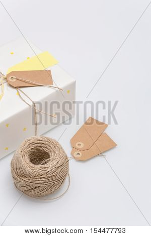 Nice present packed in white paper with small yellow stars on white background. Wrapped gift for birthday party. Flat lay. Mock-up. Holidays concept.