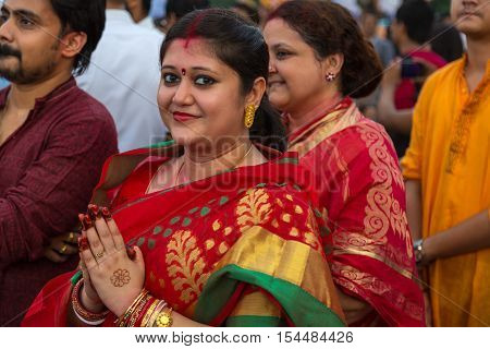 OLKATA, INDIA - OCTOBER 10, 2016: A hindu married woman holds her hands to pay homage to Goddess Durga at the  immersion ceremony at Babughat Kolkata, West Bengal, India.