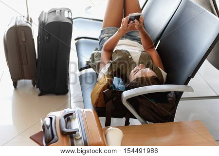 Carefree young girl is entreating with mobile phone at airport. She is lying on chairs near baggage with relaxation