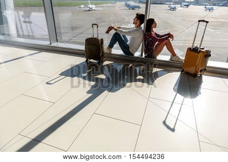 Tired young man and woman are waiting for flight. They are sitting near window at airport. Their eyes are closed