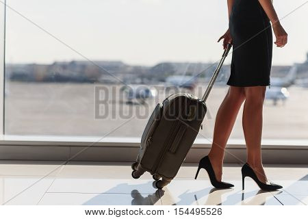 Close up of legs of elegant woman going on business trip. She is standing in airport and carrying suitcase