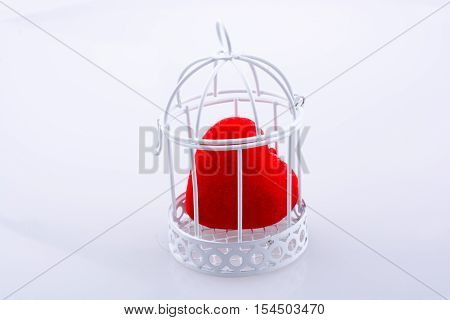 Red heart shape icon in metal wired cage
