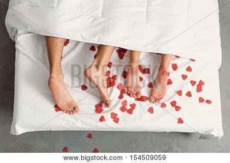Close up of male and female feet. Loving couple is lying on bed under blanket covered by small red paper hearts