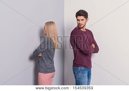 First quarrel. Young man and woman are offended at each other. They are standing with crossed hands. Isolated