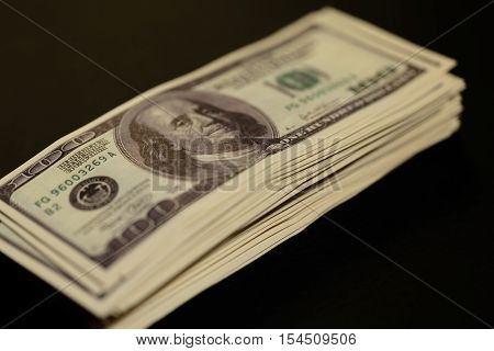 stack of one hundred dollar bills increases on a dark background. bundle of money
