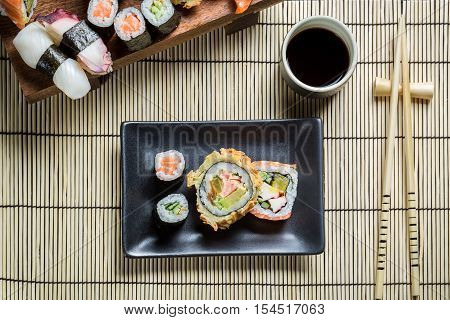 Fresh sushi served with soy sauce on old wooden table
