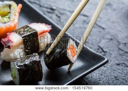 Sushi eaten with chopsticks on black rock