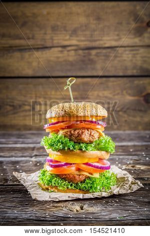 Big and tasty double-decker burger on old wooden table