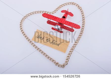 Chain forms a heart shape with a title back to school in it with a red model airplane