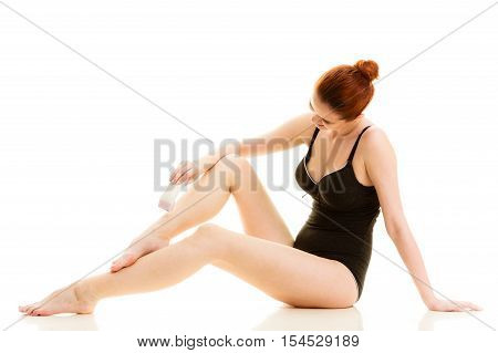 Depilation epilation hygiene concept. Redhead woman shaving her legs with electric shaver depilator wearing black swimsuit isolated.