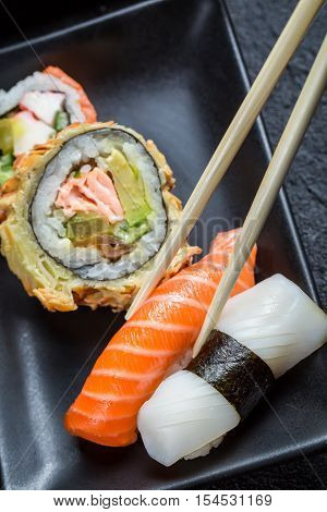 Fresh sushi eaten with chopsticks on black rock