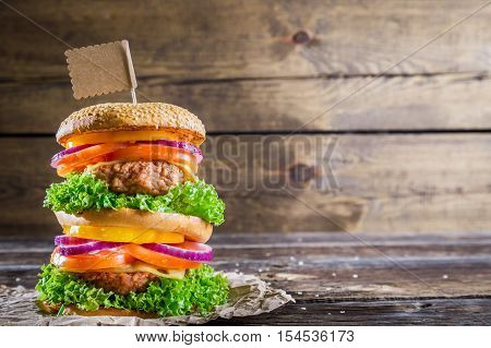 Homemade double-decker burger on old wooden table