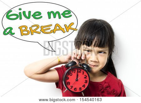 Angry Asian baby girl is holding a clock asking for a lunch break. An unhappy little girl telling you to Give Me a Break. Asian Student is stressed out and asking for a Break.