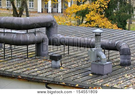 Seam roof with vent pipes and shafts in autumn.