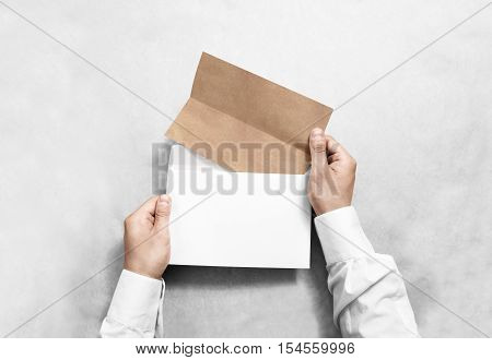 Hand holding white blank envelope and folded craft leaflet mockup, isolated. Arm hold empty brochure template mock up. Greeting card flyer design. Invitation printing display. Reading writing.