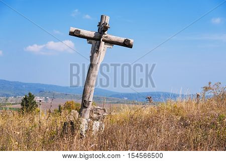 Old abandoned wooden holy cross over the blue sky