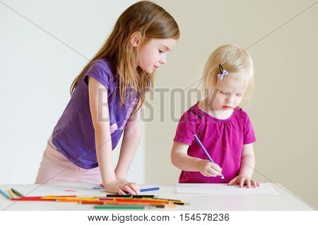 Two Little Sisters Drawing With Colorful Pencils