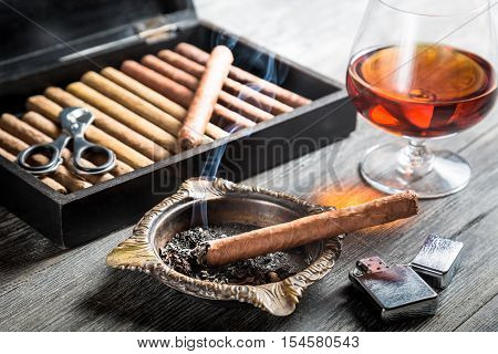 Aroma of cognac and cigar fuming on old wooden table