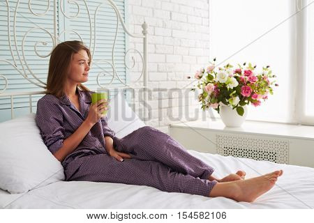 Portrait of beautiful woman on white bed holding a cup of tea and looking in the window with thoughtful expression on her face