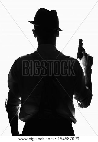 Silhouette of a private detective with a gun in right hand. Agent in stylish hat back to camera. He wears shirt with sleeves rolled to the elbow. Criminal scene in black and white. Nice studio shot.