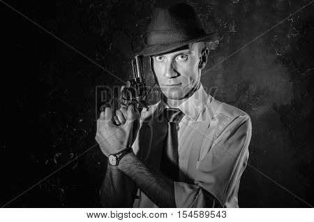 Black and white picture of a private detective with a gun in both hands. Agent in stylish hat. Man stays front to camera. He wears classic shirt with sleeves rolled to the elbow suspenders and dark tie. Criminal scene in black and white. Nice studio shot.