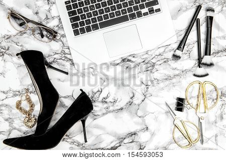 Feminine accessories notebook shoes office supplies on bright marble table background. Fashion flat lay for blogger social media