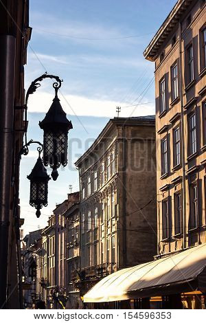Beautiful old Iron lantern wall against blue sky old stone narrow pictorial street twilight old town near central square Lviv, Ukraine. Characteristic phenomenon medieval architecture Central European