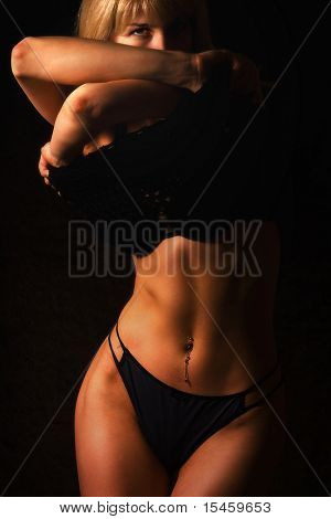 blond woman in dark undressing
