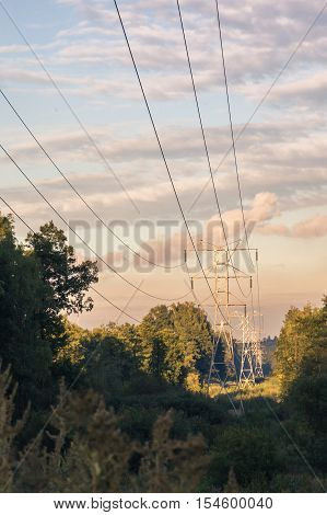 Power transmission tower 110kv on background greenery on a summer evening