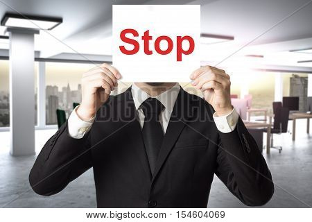 businessman modern office hiding face behind sign stop