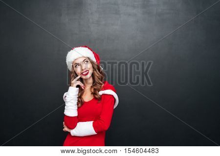 Portrait of beautiful wondered woman in red dress and hat looking away isolated on a black background