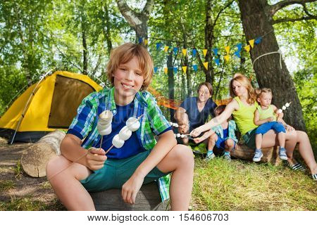 Portrait of happy smiling boy holding grilled marshmallow on a sticks at the campsite