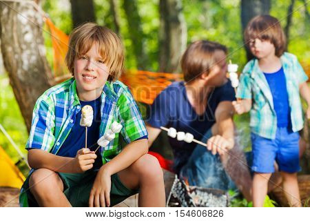 Close-up portrait of smiling teenage boy holding two sticks with grilled marshmallow at campsite in summer