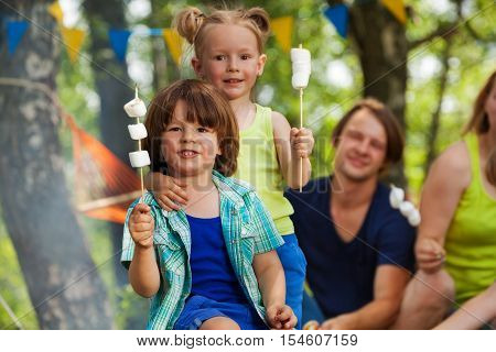 Close-up portrait of two cute kids, holding sticks of roasted marshmallow at campsite in summer