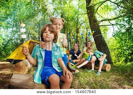 Portrait of two happy kids, three years old boy and girl, holding roasted smors on sticks at the campsite