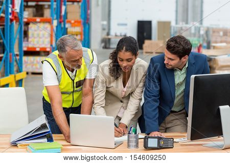 Warehouse managers and worker discussing with laptop in warehouse office