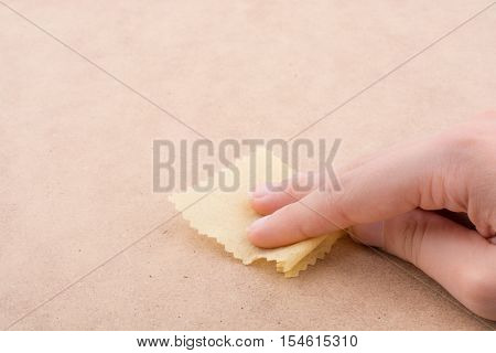 Yellow color mini handkerchief in hand on brown background